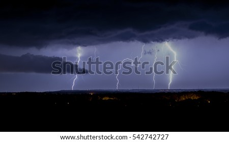 Lightning storm over city in purple light background