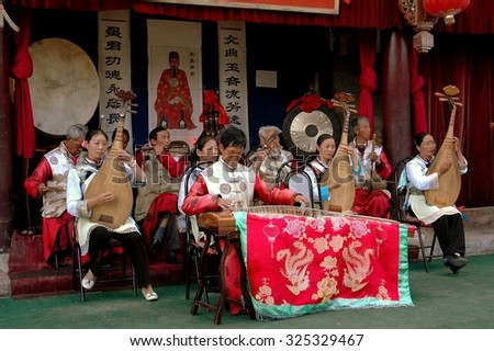 Lijiang, China - April 19, 2006:  An orchestral ensemble of musicians in traditional Naxi people clothing giving a concert at the historic House of Mu