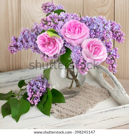Lilac flowers and roses in glass bottle on shabby wooden salver