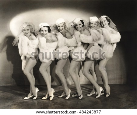 Line of chorus girls in white fur