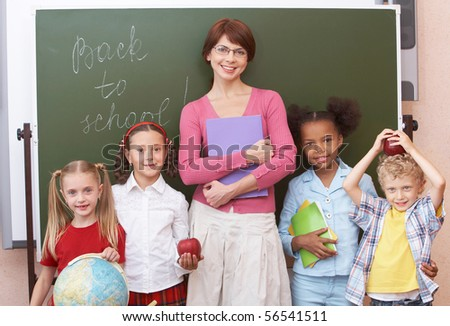Line of cute schoolchildren looking at camera with their teacher in the middle