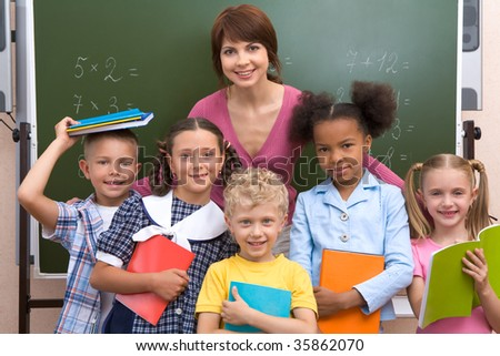 Line of smart classmates looking at camera with happy teacher behind them