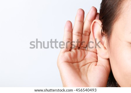 Listening female holds his hand near her ear on white background