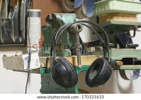 Listening to music at work concept, dirty old headphones in a carpenter's work place