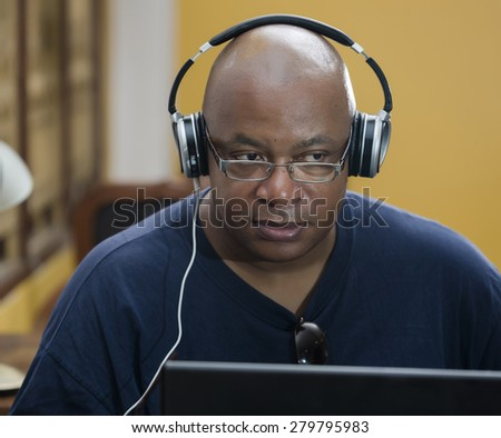 Listening to music, man concentrated with headphones