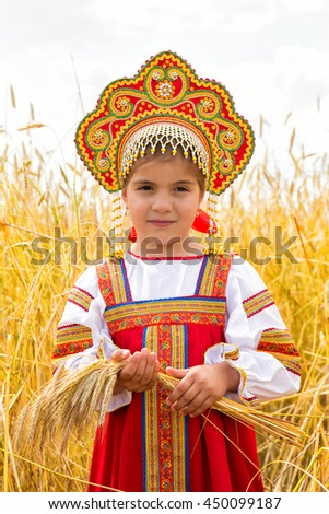 Littl girl in Russian national sarafan and a kokoshnik standing in a wheat field in summer day