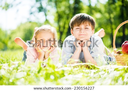 Little adorable children in park laying on grass