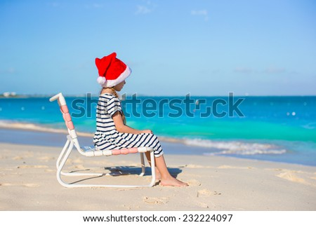 Little adorable girl wearing Santa hat at caribbean beach