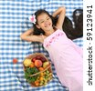Little Asian beautiful girl lying at the cloth with full basket of summer fruits - stock photo