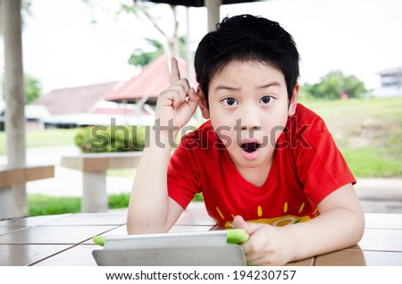 Little asian boy smiles with tablet computer on playground background .