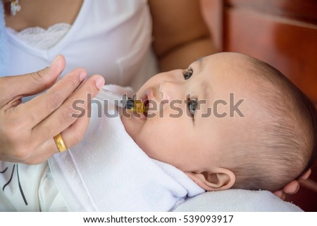 Little asian child eating medicine syrup from syringe