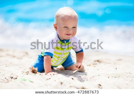 Little baby boy wearing blue rash guard suit playing on tropical ocean beach. UV and sun protection for young children. Toddler kid during family sea vacation. Summer water fun.