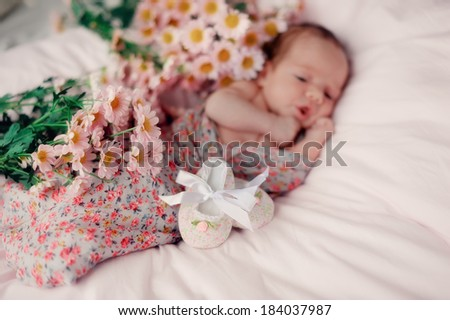 little baby wrapped in a blanket with colorful bouquet of flowers shoes