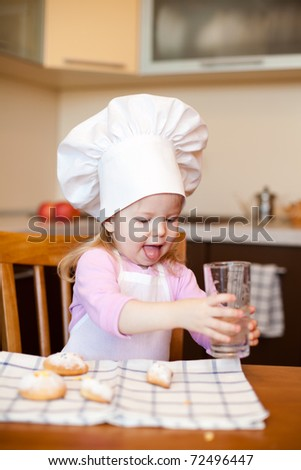 Little baker or cook girl drinks water on kitchen