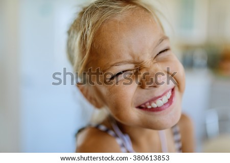 Little beautiful blonde smiling girl poses faces closeup.