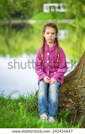 Little beautiful girl in red sweater and jeans sits near spring lake in park.
