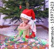 Little beautiful girl in Santa Claus hat sitting under the Christmas tree among garlands - stock photo