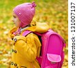 Little beautiful girl in yellow coat and pink backpack goes to school in autumn park. - stock photo
