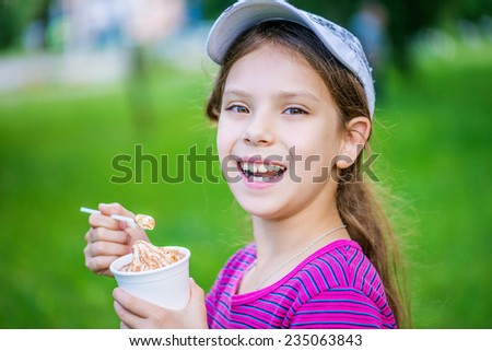 Little beautiful smiling girl holding an ice cream on background summer park.