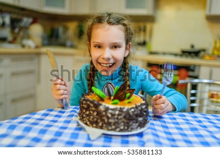 Little beautiful smiling girl with big cake on background of kitchen.