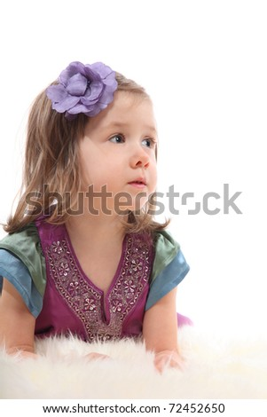Little blond girl lying on a fluffy carpet and thoughtfully looks up