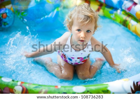 Little blondie girl in the swimming pool