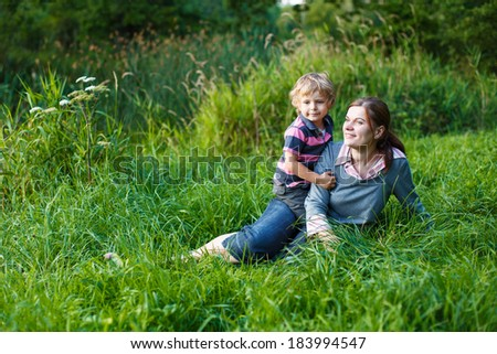 Little boy and his mother sitting on grass in summer forest near lake