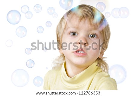 little boy and soap bubbles on white background