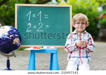 Little boy at blackboard practicing mathematics, outdoor school or nursery. Back to school concept