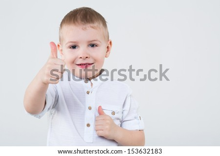 Little boy in a white shirt making thumbs up by two fists with finger in the studio