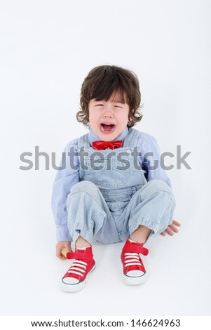 Little boy in blue jumpsuit sits on floor and cries on white background.