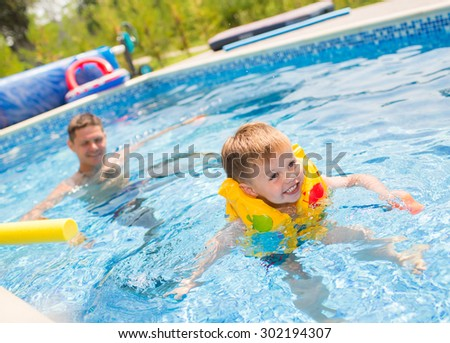 Little boy in lifevest playing in the swimming pool