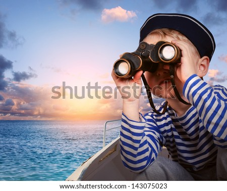 Little boy in sailor's uniform with binocular in the boat