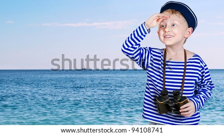 Little boy in sailor's uniform with binocular looks into the distance from the arm at the sea view background