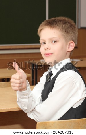 little boy in the classroom with his thumbs up
