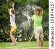 little boy is pouring a water from a hose at his sister - stock photo