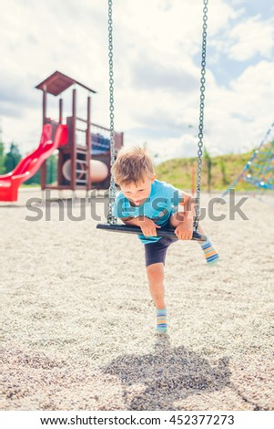 Little Boy Is Trying to Get on the Chain Swing by Himself
