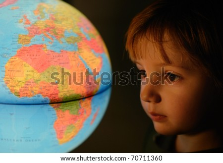 little boy looking at luminescent globe