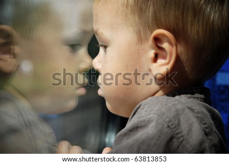 Little boy looking through window. He travels on a train.