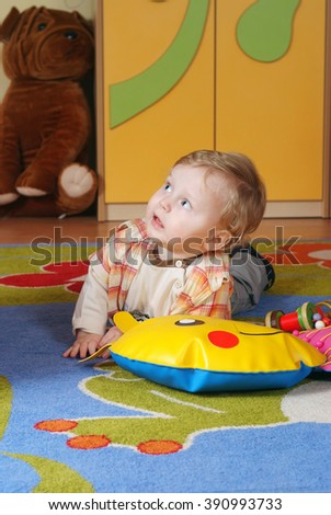 Little boy lying on the colorful carpet in nursery