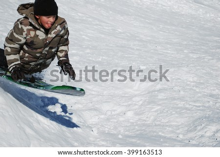 Little boy on a sled jumping a snowhill with tough out and copyspace to the right.
