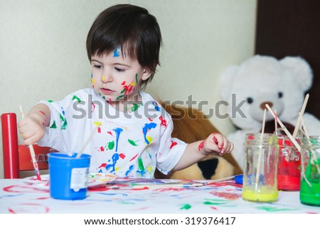 Little boy painting with paintbrush and colorful paints child