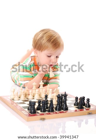 Little boy play chess on the floor.