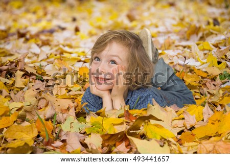 little boy playing in beautiful autumn park on warm sunny fall day. Child playing with golden maple leaves