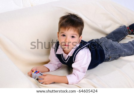 Little boy playing video games lying on the couch