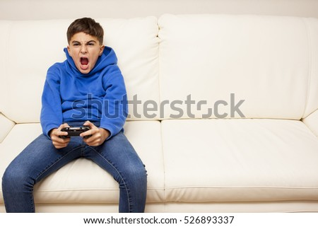 little boy playing videogame on the couch