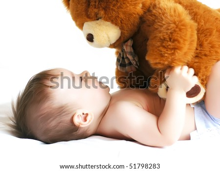 Little boy playing with a bear
