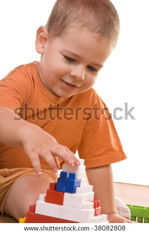 little boy playing with colorful wooden blocks
