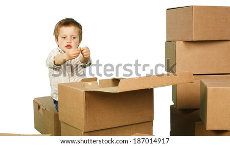 little boy plays in boxes