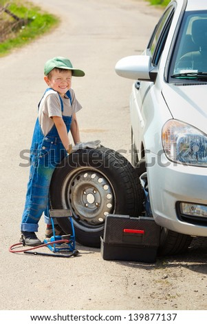 little boy repairing a car
